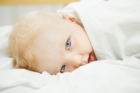 Sad baby with cold that lies covered with blanked