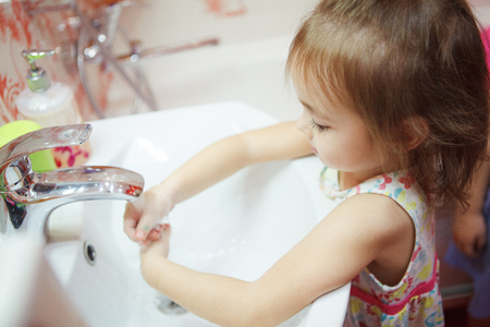 Kid wearing t-shirt washing hands in bathroom with soap