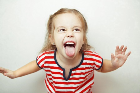 Angry little girl shows her tongue in funny grimace Stockfoto