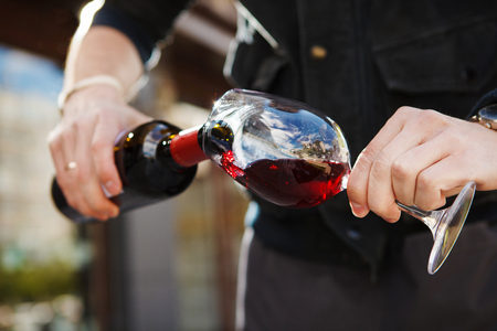 Man pouring wine into wineglass, male hand holding bottle of red expensive alcoholic beverage, closeup photo Foto de archivo
