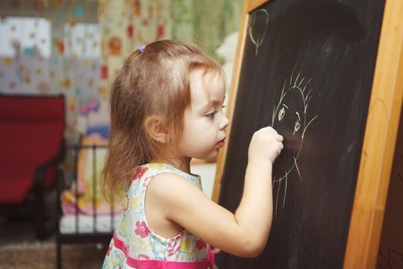 Girl with ponytail in process of drawing picture of sun
