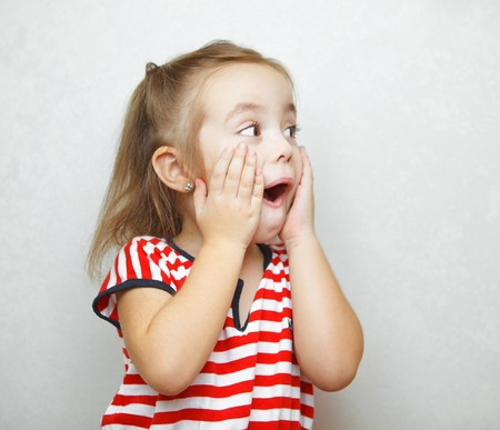 Surprised little girl with open mouth and hands on cheeks Stock Photo