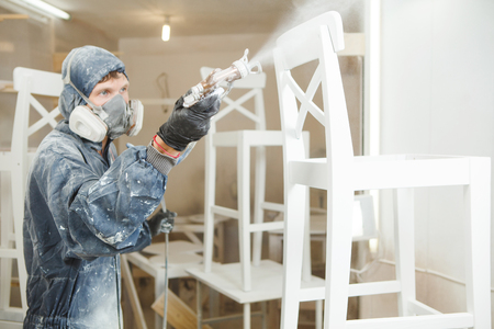 Man painting chair into white paint in respiratory mask. Application of flame retardant ensuring fire protection, airless spraying. Reklamní fotografie