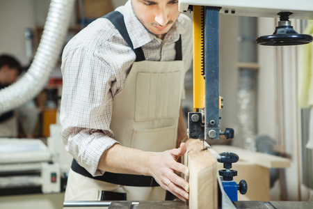 Dark-haired man holding timber on band saw