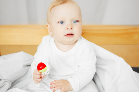 Cheerful baby sits on bed and holds rattle Stock Photo