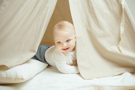 Curious child looks into the childrens tent with pillow 版權商用圖片