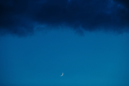 푸른 하늘과 어두운 구름의 배경에 달. 새로운 단계. 스톡 콘텐츠