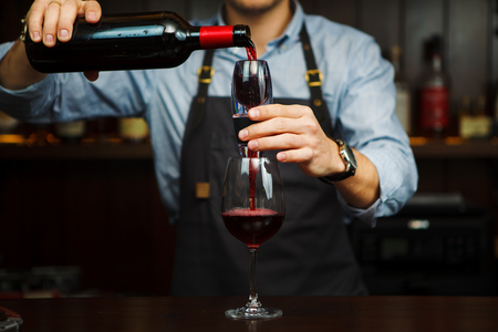 Male sommelier pouring red wine through aerator into glass. Aerators bring flavor-enhancing oxygen into drink, enhancing the flavor