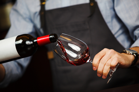 Man pouring wine into wineglass, male hand holding bottle of red expensive alcoholic beverage, closeup photo Stock Photo