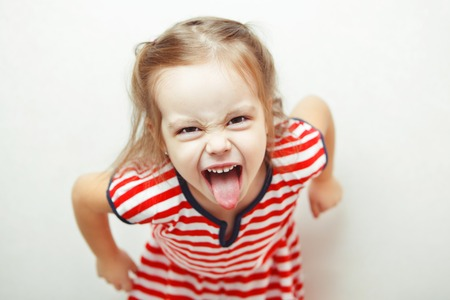Angry little girl shows her tongue in funny grimace Reklamní fotografie