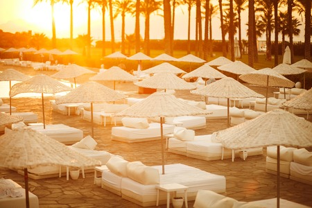 sunbeds with umbrellas at sunset. Stock Photo
