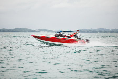 red boat sailing on the sea. beautiful and fast vessel moves open water.