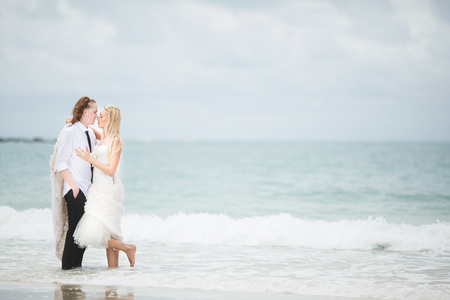bride in wedding dress and groom hugging at the sea. couple love on deserted beach. Reklamní fotografie