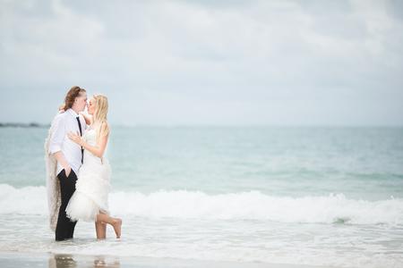 bride in wedding dress and groom hugging at the sea. couple love on deserted beach. 版權商用圖片