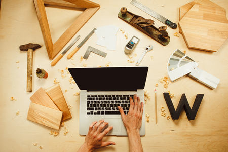 male hands typing on laptop on carpentry work tools background with wooden cuttings.