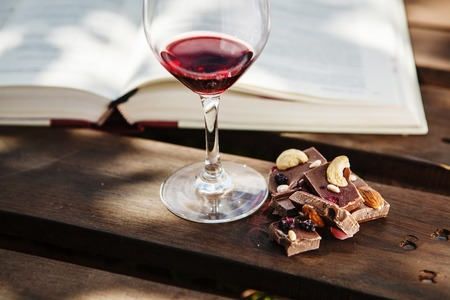 Glass with wine and pieces of chocolate near open book