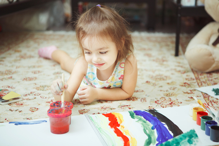 Little girl lies on bedroom floor and paint picture