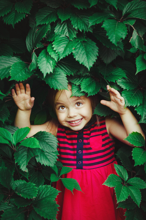 cute girl with a smile peeking out from under the green leaves.