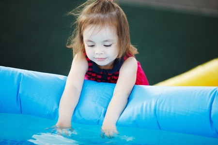 Girl with interest touches water in the pool. An inquisitive child by the water.