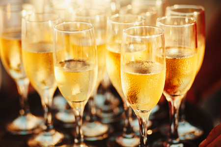 cold champagne on the tray. Sparkling wine poured by the glass. Stock Photo