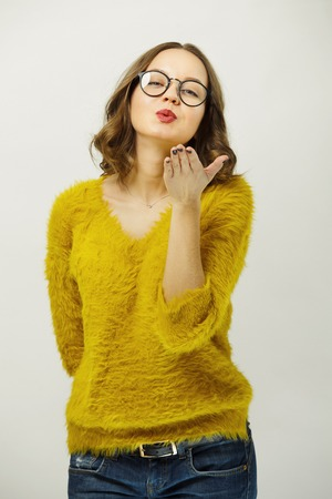 Attractive girl in bright clothes and transparent glasses sends you air kiss. Stock Photo