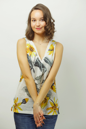 Confused girl in summer camisole is restrained with arms folded over white isolated. Stock Photo