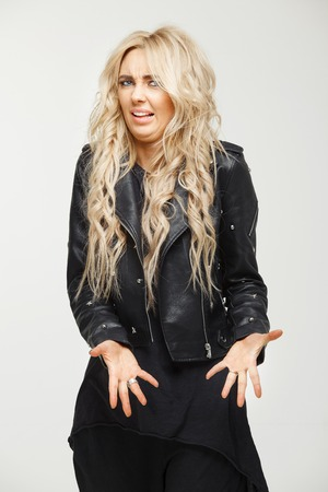 blond woman wonderfully pulls out her palms and shows disgust face on a white background. emotion of rejection and fastidiousness.