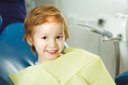 Little boy sits on dentists chair in good mood after dental procedures. Young patient with healthy teeth.