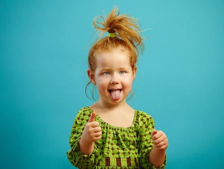 portrait of three year old girl stuck her tongue out and shows thumb up, has red hair, dressed in green dress, expresses sincere look, stands over blue isolated background. Child in good mood.
