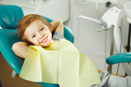 Child in good mood sitting on chair and without fear waiting dentist. Young boy is going to treat teeth. caries, fillings, teeth Banco de Imagens