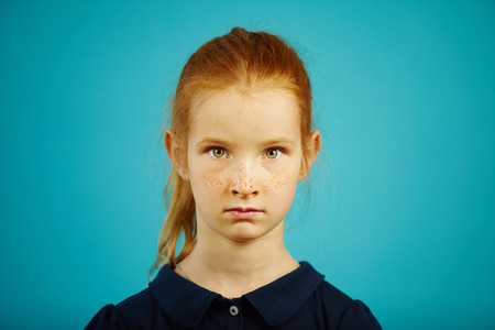 Portrait of serious seven year old girl with freckles and red hair on blue isolated background, expresses sincerity or honesty, has lovely facial features.