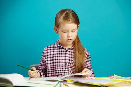Isolated portrait of obedient and diligent schoolgirl doing homework after school. Disciplined child likes to learn. Stock Photo