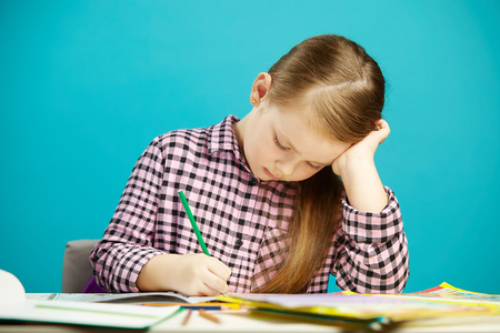 Horizontal shot of girl at desk carefully writes in notebook task, sitting over blue isolated background. Child performs homework.