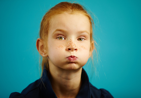Portrait of seven year old girl with inflated cheeks, has red hair and freckles, close-up shot on blue isolated background. Imagens