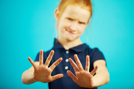 Child expresses denial by pulling his hands into the camera, showing repulsion or rejection.