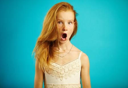 Red haired girl in white dress with surprised expression opens her mouth and eyes wide, shows a strong emotion of fear or shock, is shocked and stunned.