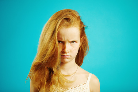 Horizontal portrait of angry red haired girl with gloomy expression demonstrates anger and dissatisfaction, has bad mood and capricious character. Stock fotó