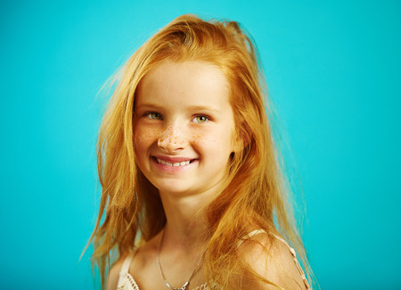 Portrait of little girl seven years old with fiery red hair, cute freckles, smiling sincerely, expresses confidence and honesty.