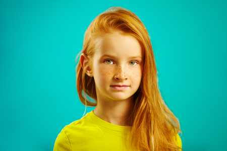 Portrait of beautiful redhead girl seven years old with freckles wearing yellow t-shirt. Stock Photo