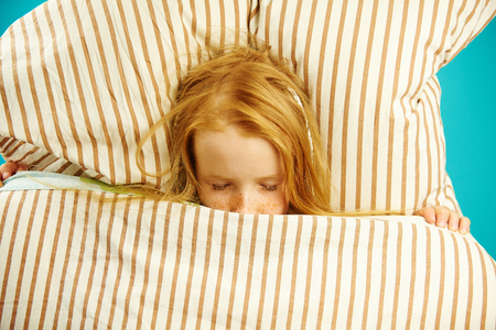 Top view of children girl lying in bed under the covers, sees pleasant dreams. Stock Photo