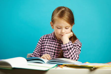 Disciplined girl attentively reads book sitting at the table, expresses her passion, on isolated blue background. Child performs home task.
