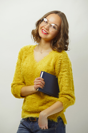 Smiling woman with bright appearance and cute expression, wearing round spectacles and colored clothes, looking at camera on white isolated. 写真素材