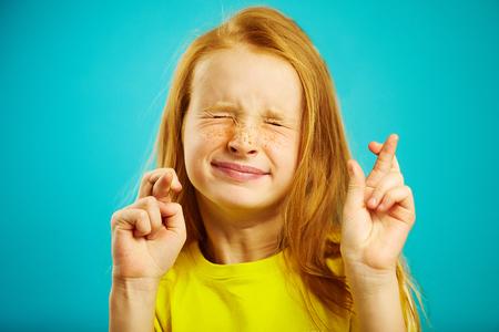 La niña de los niños cerró los ojos con fuerza y cruzó los dedos, pide un deseo, cree en el sueño, expresa emociones sinceras, tiene rasgos faciales divertidos, hermoso cabello rojo con pecas. Foto de archivo