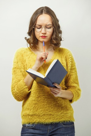 puzzled woman looking at diary with disgruntled expression, demonstrating frustration or complexity of solution over white isolated.