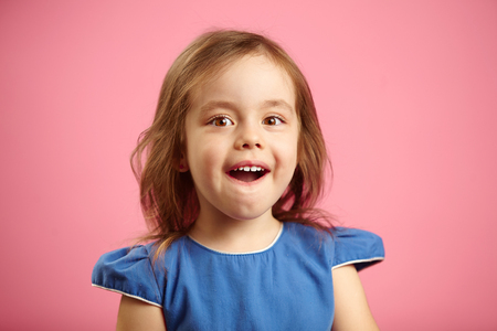 Isolated portrait of surprised girl three years old on pink isolated background. Small child expresses sincere emotions of astonishment and amazement, opens his mouth.