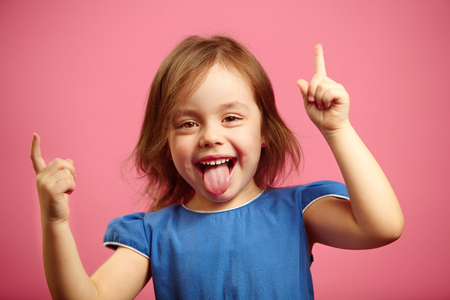 Cheerful little girl dancing with her hands raised and tongue sticking out, portrait of joyful female child over pink background.