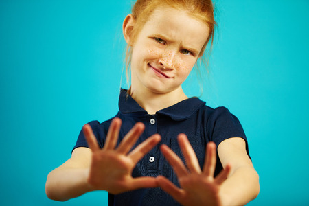 Portrait of little girl with dissatisfied expression of denial pulls her hands into the camera, showing repulsion or rejection.