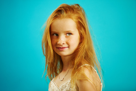 Shot of red-haired girl of seven years old with beautiful look stands sideways and looks past the camera, has a cute expression. Фото со стока