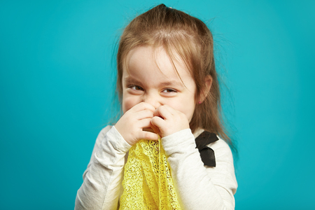 Laughing little girl covers her face with hands, smiles coquettishly and shyly, expresses embarrassment and shyness, portrait of cheerful female child on blue background. Stockfoto