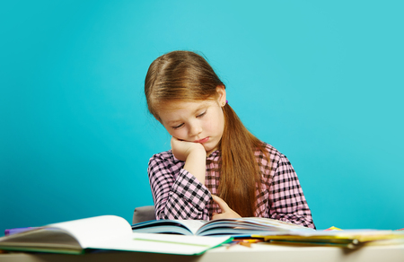 Tired girl in weary state reads book at her desk and experiences dissatisfaction. Lazy student does not want to learn.